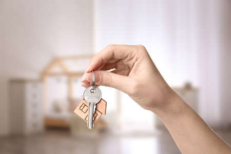 Woman holding house key on blurred background, closeup Stock Photo