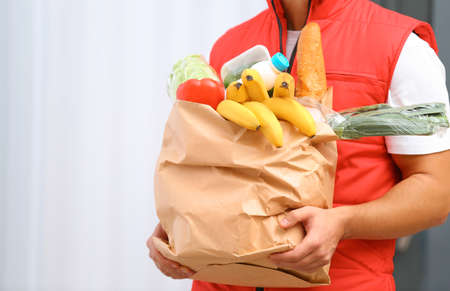 Food delivery courier holding paper bag with products indoors, closeup. Space for text
