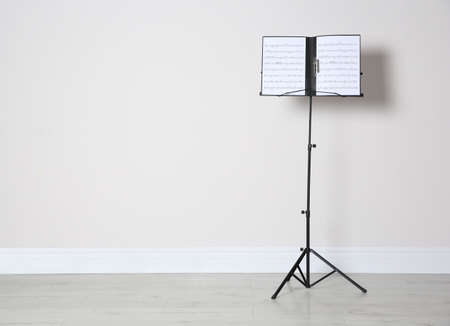 Note stand with music sheets near white wall indoors. Space for text 版權商用圖片