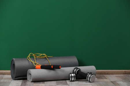 Fitnessgeräte auf dem Boden in der Nähe der Farbwand. Platz für Text
