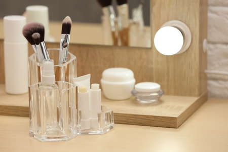 Organizer with cosmetic products and makeup accessories on dressing table indoors 免版税图像
