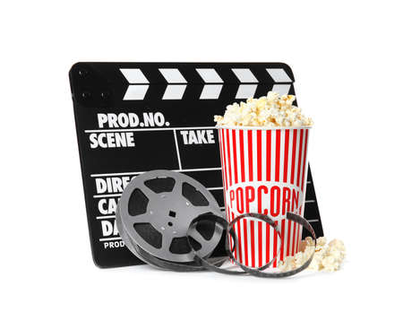 Popcorn, clapper and reel isolated on white. Cinema snack Stock Photo