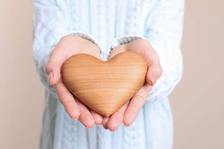 Young woman holding wooden heart in hands, closeup view