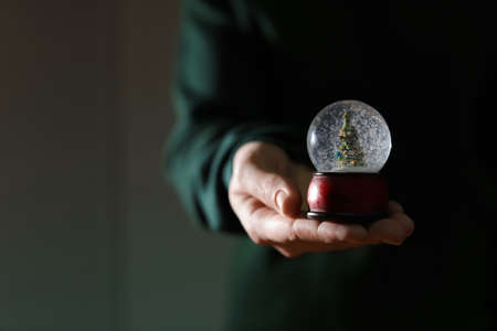 Woman holding Christmas snow globe on blurred background, closeup. Space for text