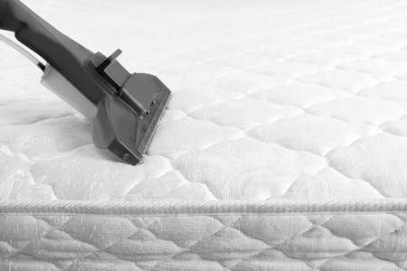 Using modern vacuum cleaner for mattress disinfection, closeup. Space for text