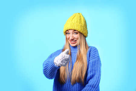 Portrait of emotional young woman in stylish hat, sweater and mittens on color background. Winter atmosphere Stock Photo