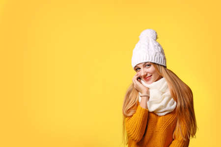 Portrait of emotional young woman in stylish hat, sweater and scarf on color background, space for text. Winter atmosphere Stock Photo