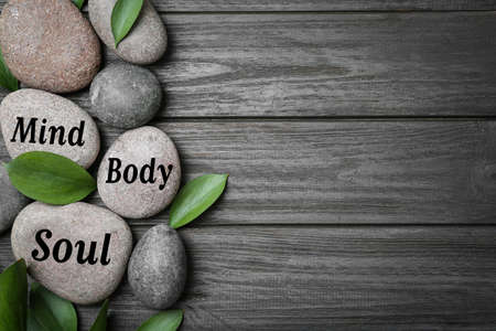 Flat lay composition of zen stones with words Mind, Body, Soul on wooden background. Space for text