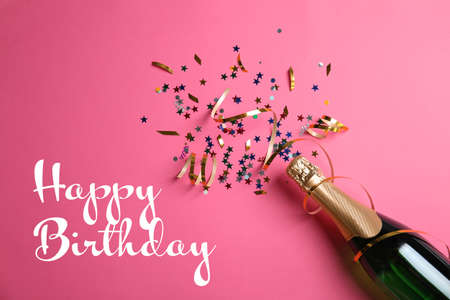 Flat lay composition with bottle of champagne and text Happy Birthday on pink background Archivio Fotografico
