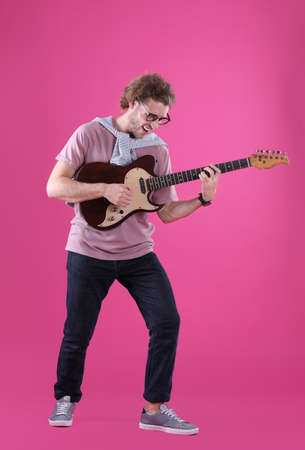 Young man playing electric guitar on color background