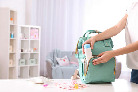 Woman packing baby accessories into maternity backpack on table indoors, closeup. Space for text
