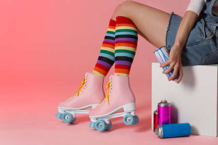 Woman with vintage roller skates and spray paint cans on color background, closeup. Space for text Фото со стока