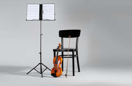 Violin, chair and note stand with music sheets on grey background. Space for text