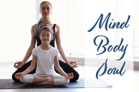 Mother with daughter practicing zen yoga in gym and text Mind, Body, Soul Imagens
