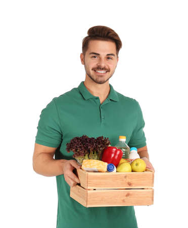 Young man holding wooden crate with products on white background. Food delivery service