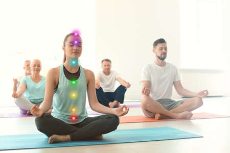 Young woman with chakra points practicing zen yoga in group indoors
