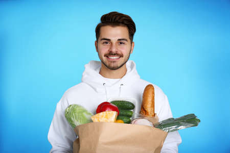 Young man holding paper bag with products on color background. Food delivery service