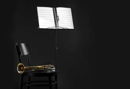 Trumpet, chair and note stand with music sheets on black background. Space for text