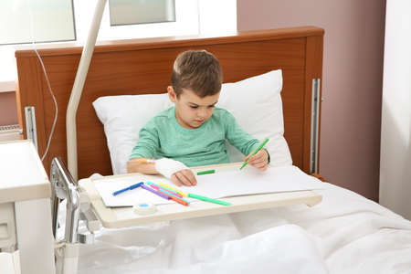Little child with intravenous drip drawing in hospital bed Stock Photo