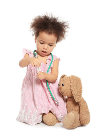 Cute African American child imagining herself as doctor while playing with stethoscope and toy bunny on white background