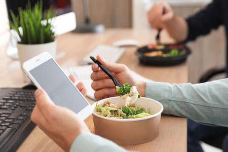 Büroangestellter mit Smartphone beim Mittagessen am Arbeitsplatz, Nahaufnahme. Lebensmittellieferservice Standard-Bild