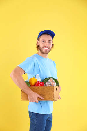 Delivery man holding wooden crate with food products on color background Imagens - 116623101