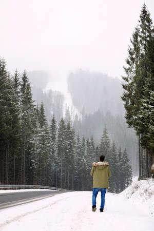 Man walking near snowy forest on winter day