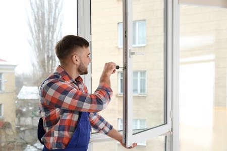 Construction worker adjusting installed window with screwdriver indoors