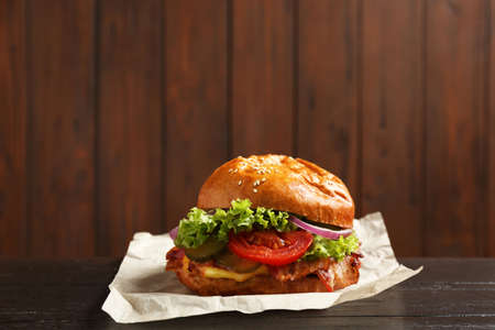 Delicious burger with bacon on table against blurred background. Space for text Stok Fotoğraf