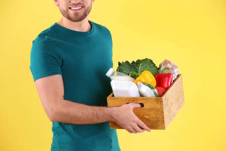 Delivery man holding wooden crate with food products on color background, closeup Stock Photo