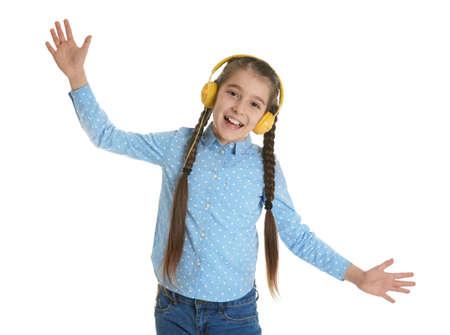 Cute little girl listening to music with headphones on white background Standard-Bild