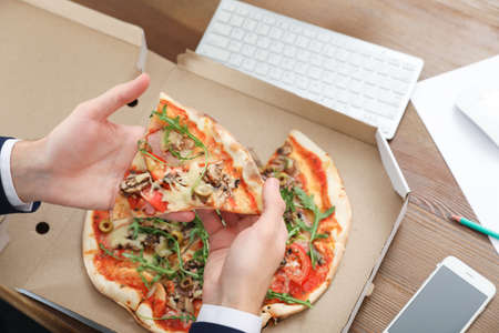 Office employee having pizza for lunch at workplace, closeup. Food delivery
