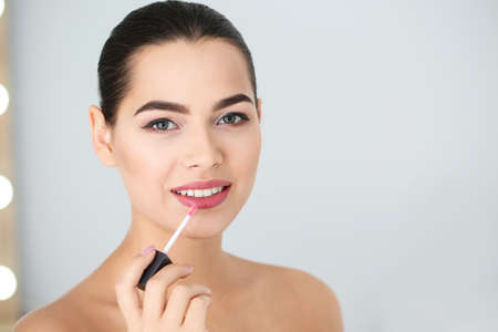 Young woman applying liquid lipstick on blurred background. Space for text Stock Photo