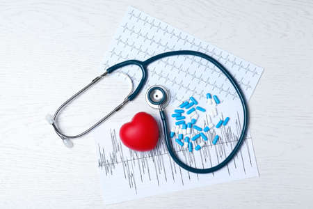 Stethoscope, heart, pills and cardiograms on wooden background, top view. Cardiology concept Foto de archivo