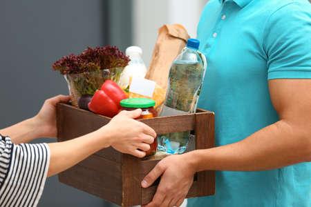 Courrier masculin livrant de la nourriture au client à l'intérieur, gros plan Banque d'images