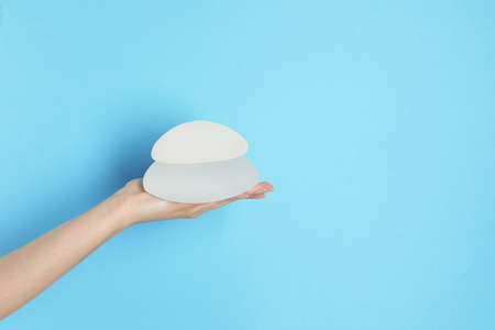 Woman holding silicone implants for breast augmentation on color background, space for text. Cosmetic surgery