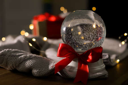 Christmas snow globe with knitting sweater on wooden table. Space for text