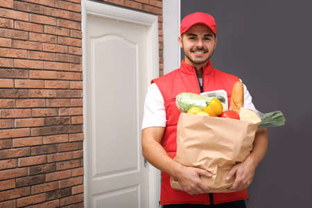 Food delivery courier holding paper bag with products indoors. Space for text