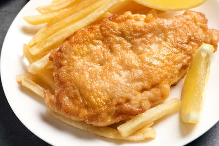 Plate with British traditional fish and potato chips, closeup