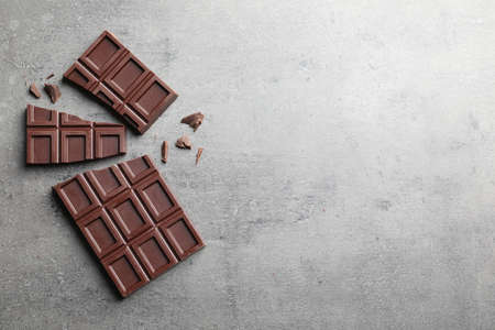 Pieces of tasty chocolate on grey background, flat lay. Space for text Reklamní fotografie