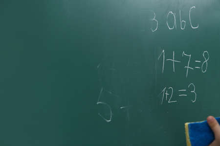 Little child wiping math sums from chalkboard, closeup. Space for text