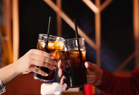 Young couple with glasses of refreshing cola indoors, closeup Banque d'images