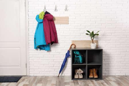 Stijlvol ganginterieur met schoenenrek en hangende kleding op bakstenen muur Stockfoto