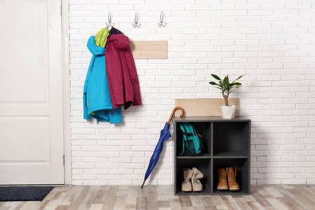Stylish hallway interior with shoe rack and hanging clothes on brick wall