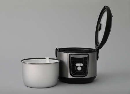 Cocina multiuso eléctrica moderna, piezas y accesorios sobre fondo gris. Espacio para texto