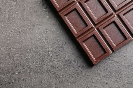 Chocolate bar on grey background, top view. Space for text Reklamní fotografie
