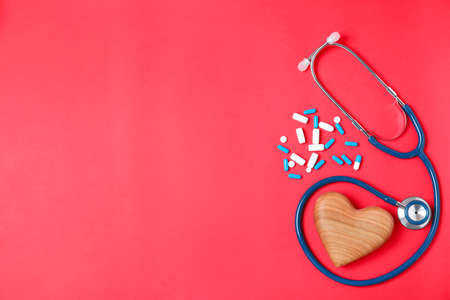 Flat lay composition with stethoscope, pills and heart on color background, space for text. Cardiology concept