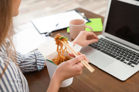 Office employee using laptop while having noodles for lunch at workplace, closeup. Food delivery 免版税图像