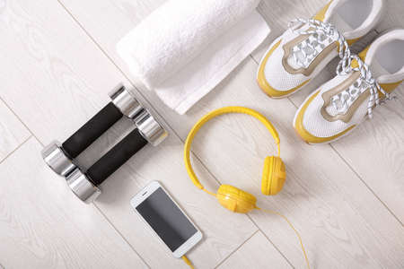 Flat lay composition with sneakers, headphones, mobile phone, towel and dumbbells on wooden background Фото со стока