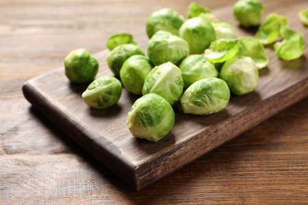 Board with Brussels sprouts on wooden table, closeup